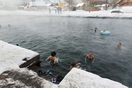 therapy geothermal: KAMCHATKA PENINSULA, RUSSIA - MARCH 8, 2013: A group of people relaxing in the winter in the public pool with natural thermal mineral water on a cloudy day. Eurasia, Russian Far East, Kamchatsky Krai, Esso Village.