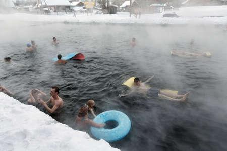 캄차카 PENINSULA, 러시아 - 2013 년 3 월 8 일 : 사람들이 흐린 날에 겨울에 천연 열 미네랄 워터와 함께 공공 수영장에서 열 온천을 가져가 라. 유라시아, 러