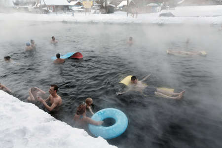 spa treatment: KAMCHATKA PENINSULA, RUSSIA - MARCH 8, 2013: People take thermal baths in the public pool with natural thermal mineral water in the winter on a cloudy day. Eurasia, Russian Far East, Kamchatsky Krai, Esso Village.