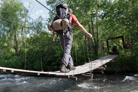Hiking on Kamchatka Peninsula: man - tourist and traveler with backpack crossing the mountain river on a pedestrian suspension bridge. Eurasia, Russian Far East, Kamchatka Region, Nalychevo.