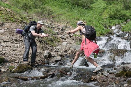 lejano oriente: KAMCHATKA, Rusia - 23 de junio de 2012: Verano senderismo - hombre de turismo ayuda a una chica-tur�stica para cruzar el r�o de monta�a en un d�a soleado de verano en la pen�nsula de Kamchatka. Eurasia, Lejano Oriente ruso, Kamchatka Regi�n.