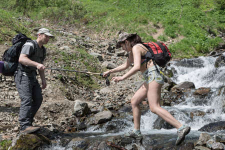 far east: KAMCHATKA PENINSULA, RUSSIA - JUNE 23, 2012: Summer hiking - tourist man helps a girl-tourist to crossing the mountain river in a summer sunny day on Kamchatka Peninsula. Eurasia, Russian Far East, Kamchatka Region. Editorial