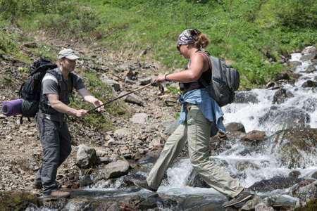 far east: KAMCHATKA PENINSULA, RUSSIA - JUNE 23, 2012: Summer hiking - tourist man helps a girl-tourist to cross the mountain river in a summer sunny day on the Kamchatka Peninsula. Eurasia, Russian Far East, Kamchatka Region.