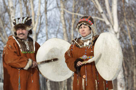 far east: KAMCHATKA, RUSSIA - FEB 5, 2012: Man and woman in the Koryak national dress stand with tambourines in the background of a winter forest. Concert Koryak National Folklore Dance Group. Eurasia, Russian Far East, Kamchatka Region.