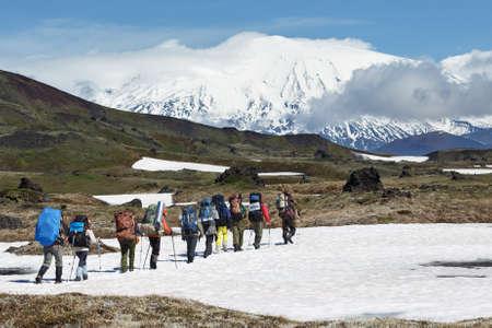 Hiking on Kamchatka: group of hiker with backpack goes in mountain on background of beautiful Klyuchevskaya Group of Volcanoes on sunny day. Kamchatka Peninsula, Russian Far East, Eurasia. Фото со стока
