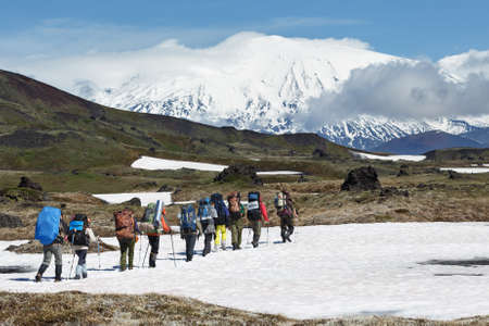 Hiking on Kamchatka: group of hiker with backpack goes in mountain on background of beautiful Klyuchevskaya Group of Volcanoes on sunny day. Kamchatka Peninsula, Russian Far East, Eurasia. Stockfoto