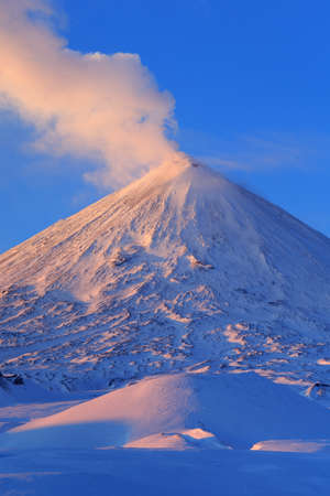 Beautiful winter volcanic landscape of Kamchatka Peninsula: view of erupting active Klyuchevskaya Sopka at sunrise. Eurasia, Russian Far East, Kamchatka Region, Klyuchevskaya Group of Volcanoes.
