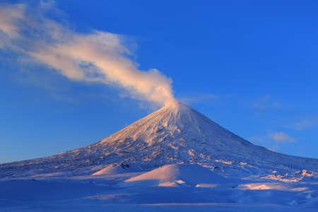 effusion: Beautiful winter volcanic landscape of Kamchatka Peninsula: view of eruption active Klyuchevskoy Volcano at sunrise. Eurasia, Russia, Far East, Kamchatka Region, Klyuchevskaya Group of Volcanoes.