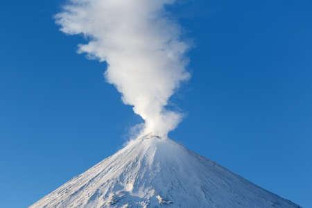lejano oriente: Invierno paisaje de la península de Kamchatka: Volcán activo Klyuchevskoy, vista de la parte superior de una erupción volcánica: la emisión del cráter del volcán del penacho de gas, vapor y cenizas. Eurasia, Lejano Oriente ruso, Kamchatsky Región, Grupo Klyuchevskaya de los volcanes.