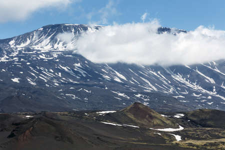volcanic landscape: Volcanic landscape of Kamchatka Peninsula: beautiful summer view of cone of active Plosky Tolbachik Volcano and clouds partially hiding the top of volcano. Eurasia, Russian Far East, Kamchatsky Region, Klyuchevskaya Group of Volcanoes.