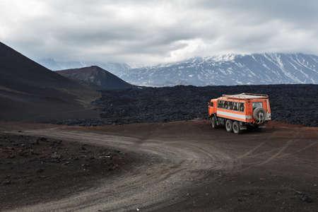 lejano oriente: Península de Kamchatka, Rusia - 24 de junio, 2016: Rusia camión de expedición KamAZ (unidad 6 ruedas) en carretera de montaña en el fondo de los campos de lava y volcanes. Eurasia, Extremo Oriente, Rusia, Kamchatka Región, Grupo Klyuchevskaya de los volcanes. Editorial