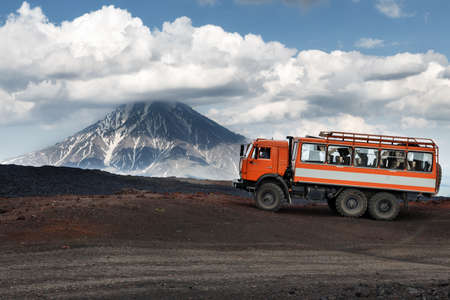 lejano oriente: KAMCHATKA, RUSSIA - JUNE 24, 2016: Russian expedition truck KamAZ (6-wheel drive) on mountain road on background of lava fields and beautiful volcano. Eurasia, Russian Federation, Far East, Kamchatka Peninsula, Klyuchevskaya Group of Volcanoes.