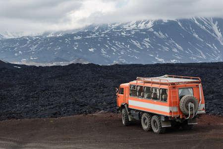 far off: KAMCHATKA PENINSULA, RUSSIA - JUNE 24, 2016: Russian expedition truck KamAZ (6-wheel drive) on mountain road on background of lava fields and volcanoes. Eurasia, Russian Far East, Kamchatka Region, Klyuchevskaya Group of Volcanoes.