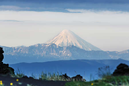 Beautiful summer volcanic landscape of Kamchatka Peninsula: view of active Kronotskaya Sopka (Kronotsky Volcano) in good weather at sunrise. Eurasia, Russian Far East, Kamchatka Region.