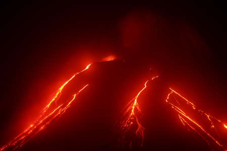 Volcanic landscape of Kamchatka: night view of eruption Klyuchevskaya Sopka, current lava flows on the slope of the volcano. Russian Far East, Kamchatka Region, Klyuchevskaya Group of Volcanoes. Stock Photo