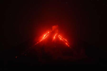 lejano oriente: Vista nocturna de la erupción del Volcán Klyuchevskoy, lava la corriente fluye en la ladera del volcán. Eurasia, Lejano Oriente ruso, Península de Kamchatka, Grupo Klyuchevskaya de los volcanes. Foto de archivo
