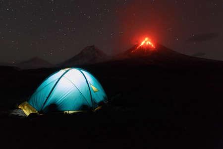 effusion: Volcanic landscape of Kamchatka: night view of illuminated tourist tent on background eruption Klyuchevskoy Volcano. Eurasia, Russia, Far East, Kamchatka Peninsula, Klyuchevskaya Group of Volcanoes.