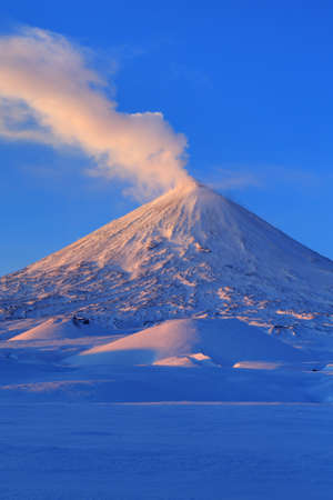 effusion: Picturesque winter volcanic landscape of Kamchatka Peninsula: view of eruption active Klyuchevskoy Volcano at sunrise. Eurasia, Russia, Far East, Kamchatsky Region, Klyuchevskaya Group of Volcanoes.