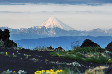 volcanic landscape: Beautiful summer volcanic landscape of Kamchatka: view of active Kronotsky Volcano (Kronotskaya Sopka) in clear weather, sunny day. Eurasia, Russia, Far East, Kamchatka Peninsula. Stock Photo