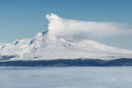 effusion: Volcanic landscape of Kamchatka Peninsula: erupting active Shiveluch Volcano in explosion of magmatic gases, accompanied by release of crater of volcano of large masses of steam, ash. Eurasia, Russia, Far East, Kamchatka Region. Stock Photo