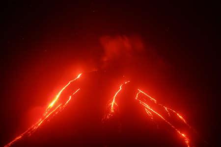 Volcanic landscape of Kamchatka Peninsula: night view of eruption Klyuchevskoy Volcano, current lava flows on slope of volcano. Eurasia, Russia, Far East, Kamchatka, Klyuchevskaya Group of Volcanoes. Stock Photo