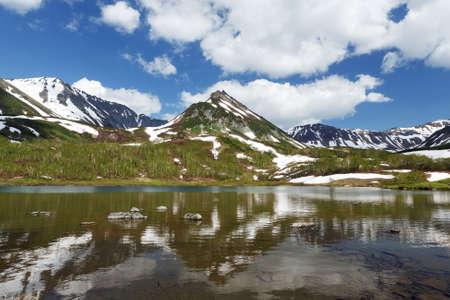 lejano oriente: paisaje de verano de Kamchatka: vista de la cordillera Vachkazhets y las nubes en el cielo azul, la reflexión en el lago de la montaña en un día soleado. Eurasia, Lejano Oriente ruso, península de Kamchatka.