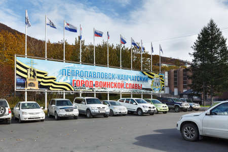 flagpoles: PETROPAVLOVSK-KAMCHATSKY CITY, KAMCHATKA, RUSSIA - OCTOBER 12, 2016: Poster Petropavlovsk-Kamchatsky - City of Military Glory, and flagpoles with flying official flags of Russia, Kamchatka Region and Petropavlovsk-Kamchatsky City District.