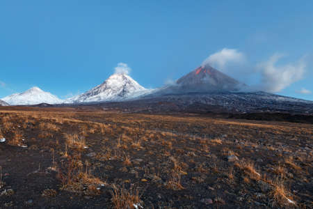 eruptive: Volcanic landscape of Kamchatka Peninsula: view of eruption Klyuchevskoy Volcano, lava flows on slope of volcano; plume of gas, steam, ash from crater. Russian Far East, Klyuchevskaya Group of Volcanoes. Stock Photo