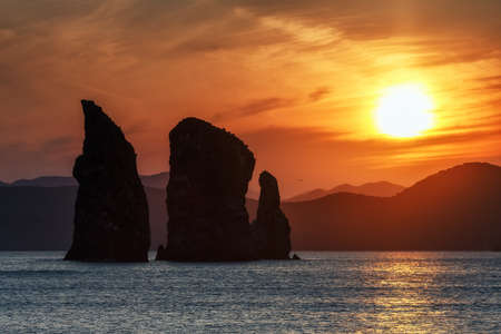Kamchatka seascape: beautiful view of Three Brothers Rocks in Avachinskaya Bay (Pacific Ocean) at sunset. Kamchatka Peninsula, Russian Far East, Eurasia.