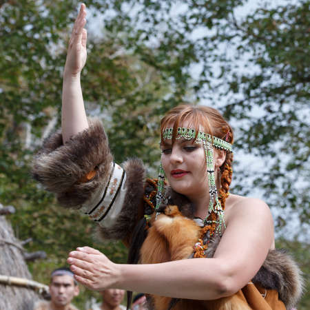 KAMCHATKA REGION, RUSSIA - SEP 14, 2013: Concert on Itelmen national holiday of thanksgiving nature Alhalalalay. Expression young woman (ensemble Northern Dawns) dancing in clothing aborigine of Kamchatka.