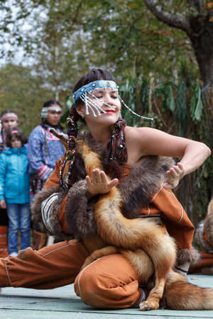 dawns: KAMCHATKA PENINSULA, RUSSIA - SEP 14, 2013: Public concert on Itelmen national holiday of thanksgiving nature Alhalalalay. Expression young woman (ensemble Northern Dawns) dancing in clothing aborigine of Kamchatka.