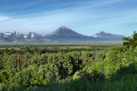 Kamchatka Peninsula summer landscape: beautiful view of Avachinsky-Koryaksky Group of Volcanoes, green forest and blue sky on sunny day. Kamchatka Region, Russian Far East, Eurasia. Stock Photo