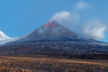 effusion: Volcanic landscape of Kamchatka: eruption Klyuchevskoy Volcano, lava flows on slope of volcano; plume of gas, steam, ash from crater. Kamchatka Peninsula, Russia, Klyuchevskaya Group of Volcanoes. Stock Photo