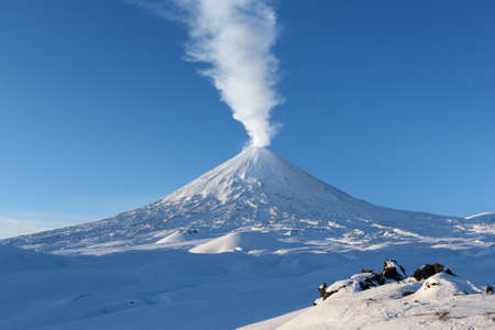 Winter volcanic landscape of Kamchatka Peninsula: view of eruption active Klyuchevskoy Volcano (Klyuchevskaya Sopka) - emission from crater of volcano plume of steam, gas and ashes. Russian Far East. Stock Photo