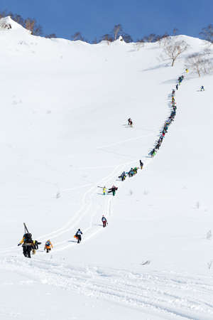 freerider: KAMCHATKA PENINSULA, RUSSIA - MARCH 9, 2014: Large group of sportsmens - skiers and snowboarders climbing the steep mountain for freeride. Competition Kamchatka Freeride Open Cup on Russian Far East.
