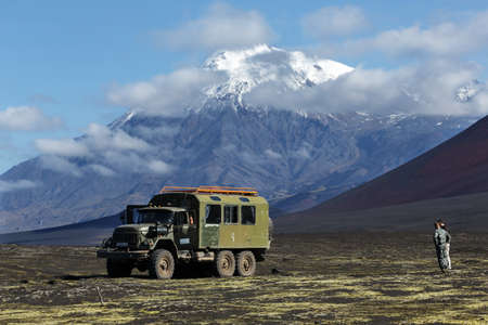 TOLBACHIK VOLCANO, KAMCHATKA PENINSULA, RUSSIA - AUGUST 27, 2014: Old soviet extreme expedition truck ZIL-131 (six-wheel drive) on volcanic slag field on background of beautiful volcano. Russia, Kamchatka Peninsula, Klyuchevskaya Group of Volcanoes.