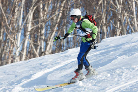 freerider: KRASNAYA SOPKA, PETROPAVLOVSK-KAMCHATSKY, KAMCHATKA, RUSSIA - FEB 4, 2012: Ski mountaineer rides skiing on mountain on forest background. Ski-mountaineering competitions - Cup Petropavlovsk City.