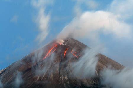 lejano oriente: paisaje volcánico: Volcán activo Klyuchevskoy, vista de la parte superior de una erupción volcánica - flujos de lava en la ladera del volcán; penacho de gas, vapor y cenizas del cráter. Península de Kamchatka, Extremo Oriente ruso, Grupo Klyuchevskaya de los volcanes. Foto de archivo