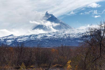 Volcanic landscape of Kamchatka: active Klyuchevskoy Volcano, view of volcanic eruption - plume of gas, steam and ash from crater. Kamchatka Peninsula, Russian Far East, Klyuchevskaya Group of Volcanoes. Stock Photo