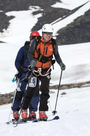 strapped: AVACHA VOLCANO, KAMCHATKA PENINSULA, RUSSIA - APRIL 21, 2012: Open Cup of Russia on Ski-Mountaineering on Kamchatka - two ski mountaineers climb on mountain on skis strapped to climbing skins.