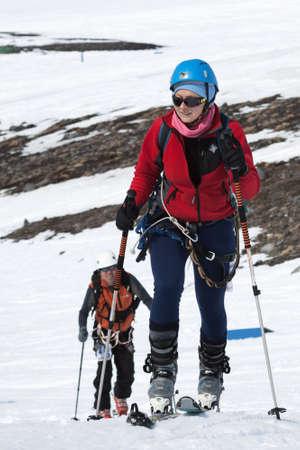 strapped: AVACHA VOLCANO, KAMCHATKA PENINSULA, RUSSIA - APRIL 21, 2012: Open Cup of Russia on Ski-Mountaineering on Kamchatka - young woman ski mountaineer climb on mountain on skis strapped to climbing skins.