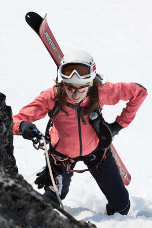 strapped: AVACHA VOLCANO, KAMCHATKA PENINSULA, RUSSIA - APR 21, 2012: Open Cup of Russia on Ski Mountaineering on Kamchatka - young woman ski mountaineer climbing on rope on rock with skis, strapped to backpack