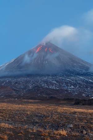 Volcanic landscape of Kamchatka: eruption Klyuchevskoy Volcano, lava flows on slope of volcano; plume of gas, steam, ash from crater. Kamchatka Peninsula, Russia, Klyuchevskaya Group of Volcanoes. Stock Photo