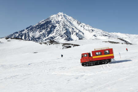 KORYAK VOLCANO, KAMCHATKA PENINSULA, RUSSIA - APRIL 26, 2014: Snowcat driving with sportsman on board (skiers and snowboarders) on snowy slopes of mountains on background of active Koryak Volcano.