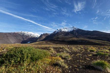 Panorama: volcanic landscape of Kamchatka - autumn view of Kozelsky Volcano on background of blue sky, beautiful clouds. Avachinsky-Koryaksky Group of Volcanoes, Kamchatka, Russian Far East, Eurasia. Stock Photo