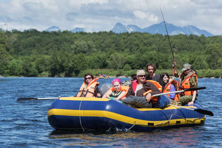 alloy: BYSTRAYA RIVER, KAMCHATKA PENINSULA, RUSSIA - JULY 13, 2016: Summer rafting on Kamchatka - group of tourists and travelers floating on calm river on raft on background of green forest and mountains.