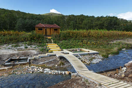 NALYCHEVO NATURE PARK, KAMCHATKA PENINSULA, RUSSIA - SEP 8, 2013: Talovskie group hot springs, thermal pools with healing mineral water, facilities for swimming outdoors tourists and travelers, with a wooden dressing room.