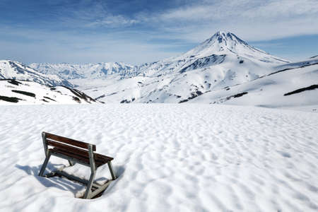 Kamchatka Peninsula volcanic landscape: wooden bench standing in snow on Vilyuchinsky Pass for rest of Kamchatka tourists and travelers, observation of Vilyuchinsky Volcano. Russian Far East. Stockfoto