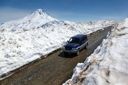 VILYUCHINSKY VOLCANO, KAMCHATKA PENINSULA, RUSSIA - JUNE 18, 2017: Japanese off-road car Mitsubishi Pajero iO driving on mountain road in snow tunnel on background of volcano. Editorial