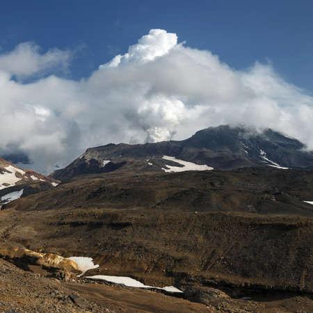 Scenery volcanic landscape of Kamchatka Peninsula: view of mountain Mutnovskaya Sopka (Mutnovsky Volcano), fumarolic activity of active volcano - clouds of smoke, steam and gas erupting from crater. Stock Photo